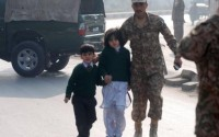 A soldier escorts schoolchildren after they were rescued from from the Army Public School that is under attack by Taliban gunmen in Peshawar