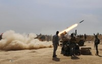 Members of the Iraqi security forces and Shi'ite fighters fire a rocket, during clashes with Islamic State militants in the town of Tal Ksaiba, near the town of al-Alam
